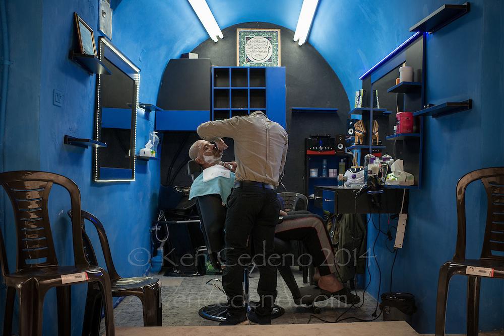 A man gets a close shave in a barber shop in Old Jerusalem, Israel April, 22, 2014. Photo Ken Cedeno