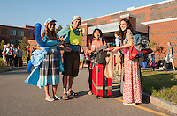 Patty and Mike Browher greet Maxine Chen from Taiwan and Ana Ulibarri from Mexico at the Laconia Middle School as Up With People arrives Monday evening.  (Karen Bobotas/for the Laconia Daily Sun)