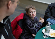 Craig Cornell, left, Ohio University's Vice President for Enrollment Management, watches as his son, Zachary Cornell, enjoys a hot dog during a pre-game tailgate for university employees in the Grover Center Atrium in Athens on Feb. 1, 2014. Photo by Lauren Pond