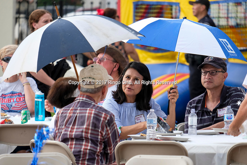 Participants with umbrellas enjoy the free food during National Night Out in San Gabriel, California, on Tuesday, Aug. 1, 2017. National Night Out is a community-police awareness-raising event in the United States and Canada, held the first Tuesday of August. Texas and Florida have the option to use the alternate date of the first Tuesday in October to avoid hot weather.(Photo by Ringo Chiu)<br /> <br /> Usage Notes: This content is intended for editorial use only. For other uses, additional clearances may be required.