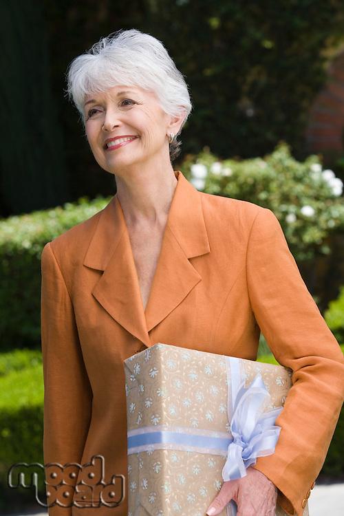 Senior woman holding present, smiling