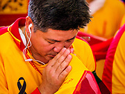 """02 JUNE 2017 - SAMUT SAKHON, THAILAND: A man prays before the City Pillar Shrine parade in Samut Sakhon. The Chaopho Lak Mueang Procession (City Pillar Shrine Procession) is a religious festival that takes place in June in front of city hall in Samut Sakhon. The """"Chaopho Lak Mueang"""" is  placed on a fishing boat and taken across the Tha Chin River from Talat Maha Chai to Tha Chalom in the area of Wat Suwannaram and then paraded through the community before returning to the temple in Samut Sakhon. Samut Sakhon is always known by its historic name of Mahachai.      PHOTO BY JACK KURTZ"""