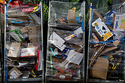 Detail of supermarket packaging and assorted materials being stored in bins outside a local Co-Op in Bellingham, on 5th February 2020, in London, England. The industrial bins are parked in front of the supermarket posters that shows fresh cabbages, and have been wrapped in plastic cling-film to contain the many boxes stacked up and awaiting collection by a recycling provider.