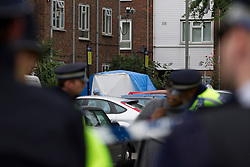 © Licensed to London News Pictures. 19/09/2013. London, UK. Police officers and a forensics tent are seen at the site of a shooting on Coppock Close in Battersea London today (19/09/2013). Taking place at around 8pm last night a 19 year old male was pronounced dead at around 9pm. Photo credit: Matt Cetti-Roberts/LNP