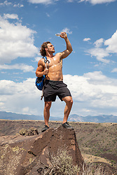 shirtless athletic man pouring water over himself to cool off on top of a mountain