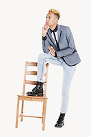 Thoughtful teenage boy standing with one leg on chair over gray background