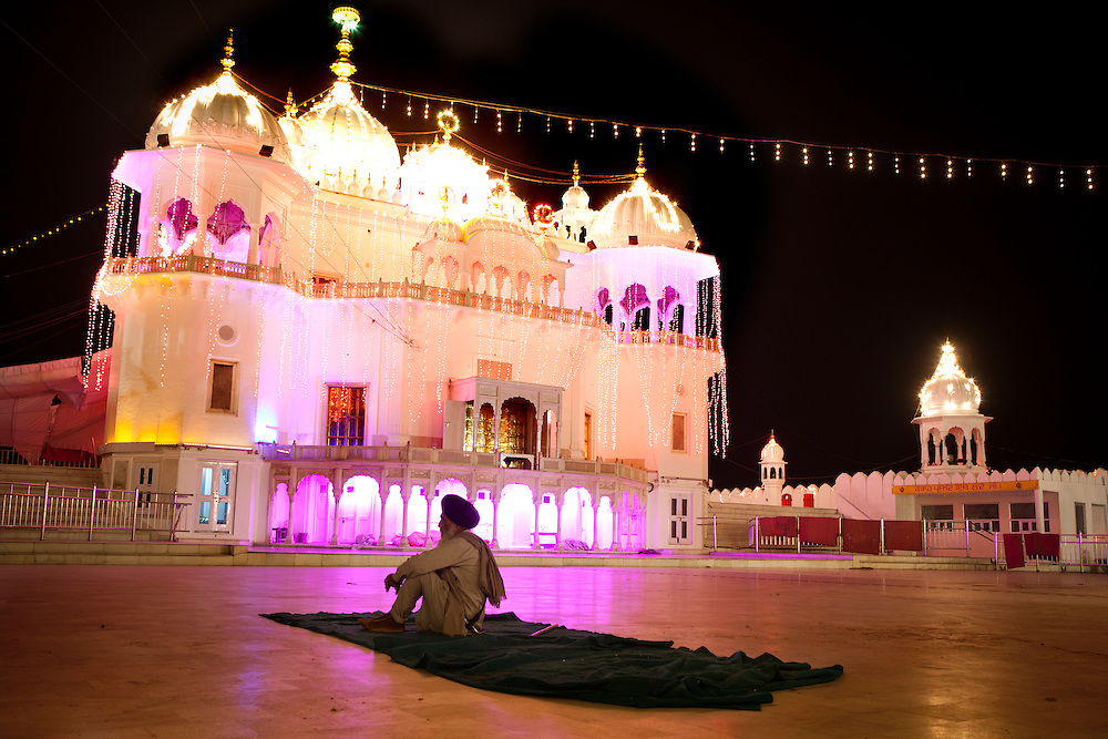 A Sikh pilgrim sits in front of a Sikh temple in Punjab, India.