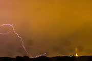 Lightning searching for a place to land above Collserola Park and the basilica at Tibidabo, Barcelona. Rain on the window.