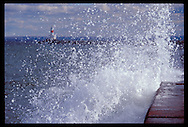 LAKE SUPERIOR WAVES CRASH ON THE UPPER HARBOR BREAKWATER WITH BREAKWATER LIGHT VISIBLE IN MARQUETTE MICHIGAN