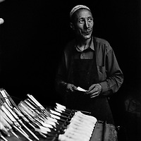 Aziz, standing behind rows of forged knives and chisels in his forge at Katman Bazaar. Katman Bazaar is a small block located in the Old city of Kashgar in the Xinjiang province of China. The Uyghur blacksmiths have worked in these quarters for hundreds of years. Like most parts of the ancient Kashgar, Katman Bazaar is now under constant danger of being demolished for the sake of urban development supported by the Chinese government.