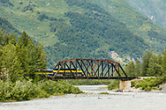 The Alaska Railroad Glacier Discovery Train crosses a bridge over the Placer River in Southcentral Alaska. Summer. Afternoon.