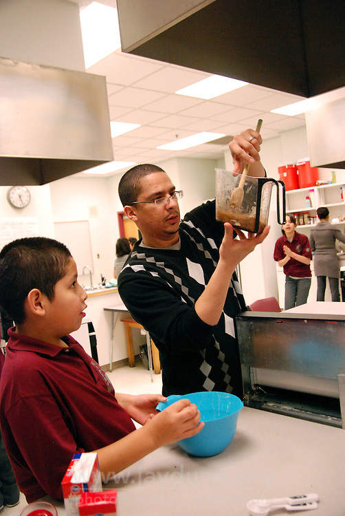 "USA, Chicago, IL, January 26, 2010.   Marlon Maya and Marcos Nieves checking ingredients. Concentrating on four crucial areas, ""Education, Violence Prevention, Cultural Enrichment, and Economic Development,"" ENLACE Chicago tries to make a positive difference to the residents of the predominantly Latino neighborhood of Little Village. Partnered with Francisco Madero Middle School, for example, ENLACE runs a comprehensive program that successfully integrates the day school with ""after-school,"" offering academic help with homework, strategies for reading, and a full schedule until 6:00 PM of enrichment programs like culinary arts, music and audio production, and contemporary dancing. Through this kind of direct outreach to more than 5,000 participants in schools and clubs, ENLACE creates opportunities and improves development in this underserved Chicago community. Photo for Hoy by Jay Dunn."