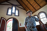 Robert Singletary describes some of the many historic features in the Sherman Chapel in Coeur d'Alene on Friday. The Chapel, which doubled as a schoolhouse for pioneers and military personnel, was built in 1880 and holds the title for the oldest standing structure in Coeur d'Alene.