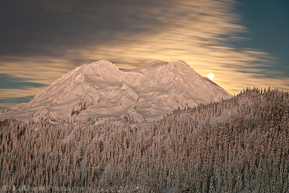 The full moon rises through clouds over Mount Rainier as viewed across the Glacier View Wilderness in the Gifford Pinchot National Forest, Cascade Mountain Range in Washington state, winter with snow covering all in the scene.