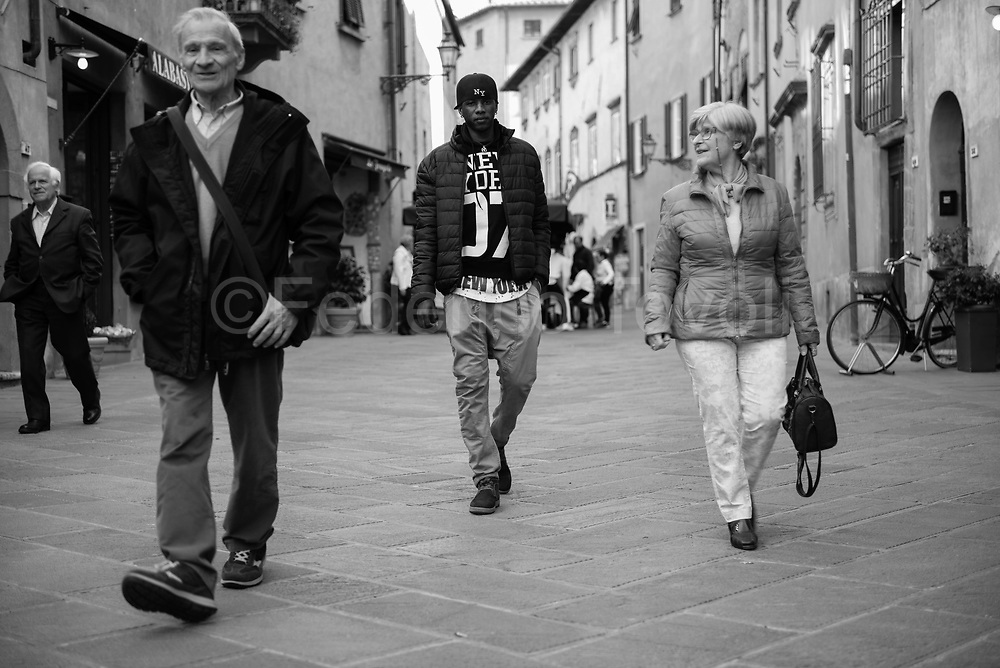 Omar Ghe from Gambia. Accomodaten by  Caritas of Volterra diocese. Walking in the main street of Volterra along with Lorenza and Igino, who are his two tutors
