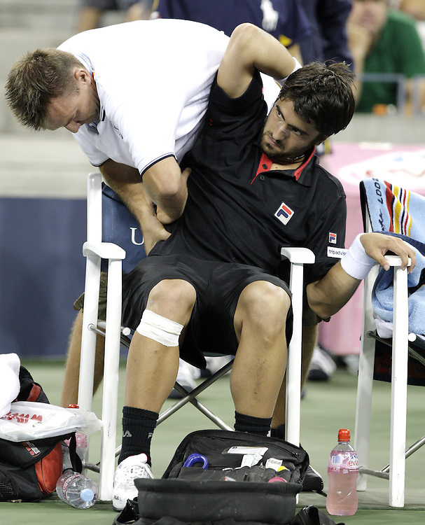 Janko Tipsarevic of Serbia (R) is tended to by a trainer during his second round match with Rafael Nadal of Spain on the fifth day of the 2007 US Open tennis tournament in Flushing Meadows, New York, USA, 31 August 2007.