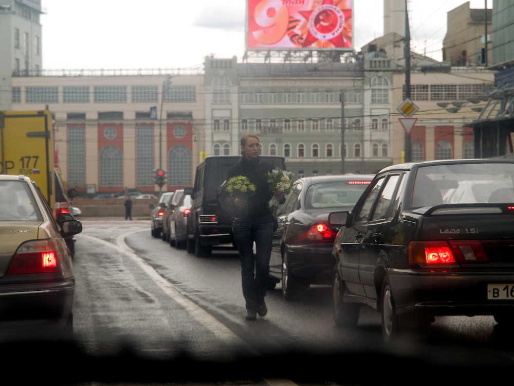 Young woman is selling flowers on a street in the center of Moscow during the afternoon rush hour.