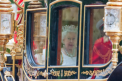 © Licensed to London News Pictures. 04/06/2014. Westminster, UK  Queen Elizabeth II being driven down The Mall in the new Diamond Jubilee State Coach to attend the State Opening of Parliament on June 4th 2014 in London. In a speech to Members of Parliament and Peers in The House of Lords, Queen Elizabeth II will officially open a new session of parliament, which will set out the government's agenda and legislation for the coming year.. Photo credit : Stephen Simpson/LNP