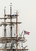 New London, Connecticut, USA - July 2012: Crew members high up in the rigging furl the sails on the Coast Guard barque Eagle when it arrives at Fort Trumbull, New London, Connecticut at the conclusion of the Parade of Sail during OpSail 2012. This is The Eagle's home port. Crew members in identical uniforms have their backs to the camera.