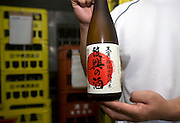 "Chief brewer Kazuhiro Ueno poses with a bottle of ""Fukko no Sake"" (Recovery Sake) at Nakayu Sake Brewery in Kami Town, Miyagi Prefecture,  Japan on 02 Sept. 2012. Photographer: Robert Gilhooly"