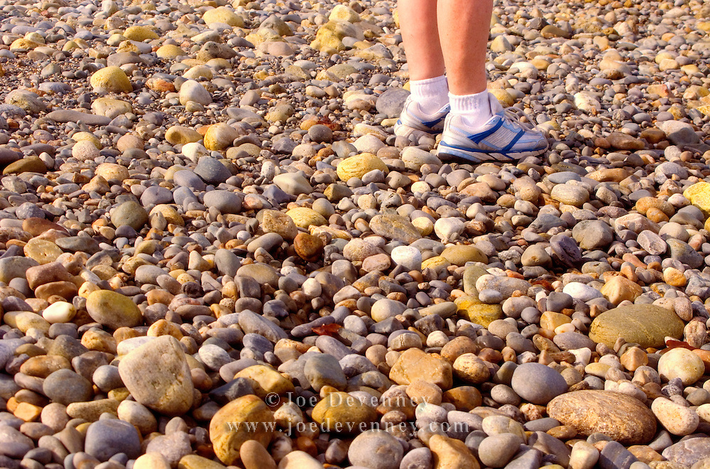 Woman wearing sneakers and standing on a rocky beach