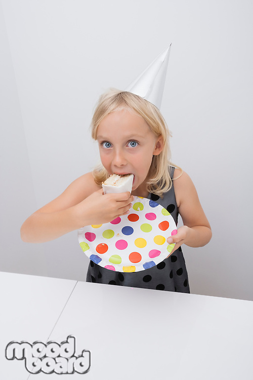 Cute girl eating birthday cake slice at table in house