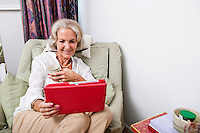Happy senior woman looking at digital tablet on armchair in house