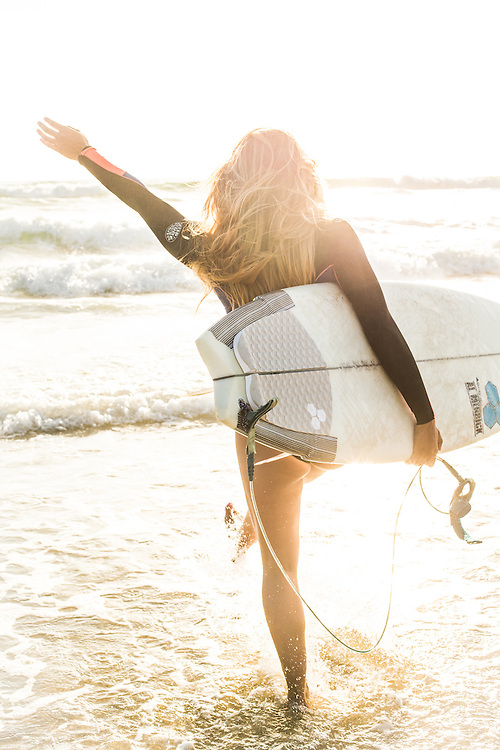 Surfer girl running into the ocean with her board in Mission Beach, San Diego, CA.