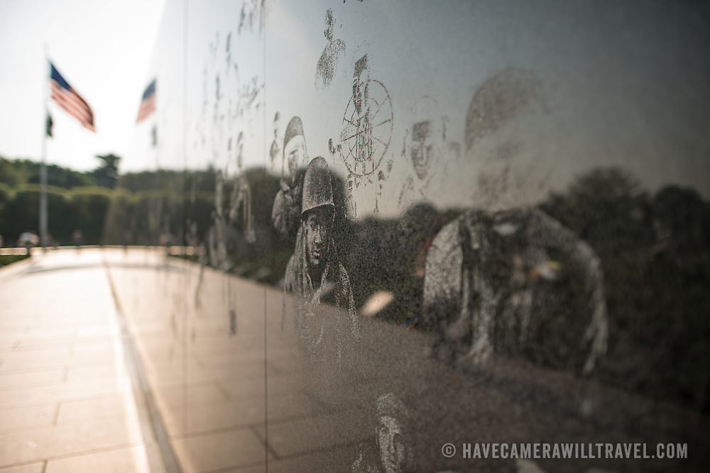 Korean War Veterans Memorial Wall Etchings. At right are some of the etchings of veterans who served in the Korean War on the wall of the Korean War Veterans Memorial on Washington DC's National Mall. At far left of frame, out of focus, is the American flag at the top of the triangle shape that bounds the memorial.