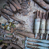 Cambodia has been dealing with the insurmountable task leftover from decades of war and its legacy, unexploded ordnance or UXOs. Estimates range from 3 to 9 million unexploded bombs that are still just beneath the surface throughout the region. These bombs are left over from air strikes, artillery fire, mortar shells, rockets, grenades, anti-personnel and anti-vehicle land mines are indiscriminate weapons and do not expire, often killing or injuring between 100 to 200 people in Cambodia a year. With little resource, the countries' people and Non Governmental Organizations (NGOs) are still facing over a hundred years being exposed to this deadly issue while walking and cultivating their land in fear.<br /> <br /> A collection of disarmed, rusted weapons, bombs and dummy RPGs at The Cambodian Landmine Museum Relief Facility's in Siem Reap, Cambodia,  Jan. 2013.