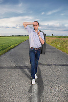 Full length of tired young man walking alone on rural road