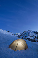 Backcountry camp with tent illuminated at twilight, North Cascades, near Hanneggan Pass, Mount Baker Wilderness Washington