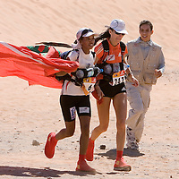 31 March 2007: #6 Didi Toura (left) of Morocco and #347 Laurence Fricotteaux (right) of France runs together to the finish line waiving Morocco national banner during sixth and final stage of the 22nd Marathon des Sables between erg Chebbi dunes and village of Merzouga (7.27 miles). Laurence Fricotteaux wins the women race, Didi Toura finishes second. The Marathon des Sables is a 6 days and 151 miles endurance race with food self sufficiency across the Sahara Desert in Morocco. Each participant must carry his, or her, own backpack containing food, sleeping gear and other material.