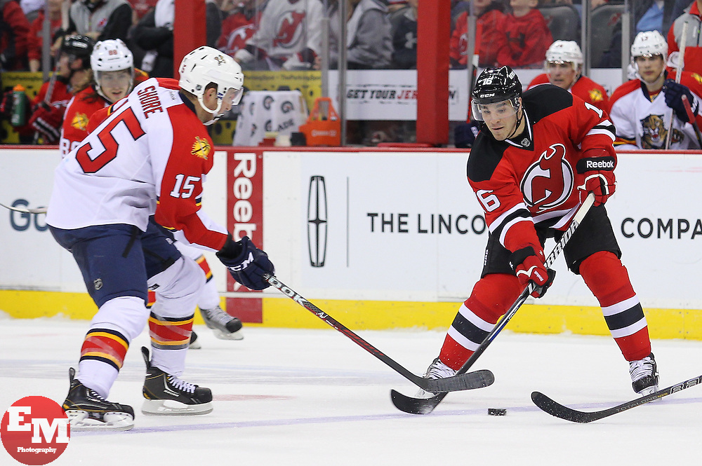 Mar 23, 2013; Newark, NJ, USA; New Jersey Devils right wing Matt D'Agostini (16) plays the puck while being defended by Florida Panthers center Drew Shore (15) during the third period at the Prudential Center. The Devils defeated the Panthers 2-1.