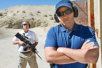 Two men at firing range in desert, portrait