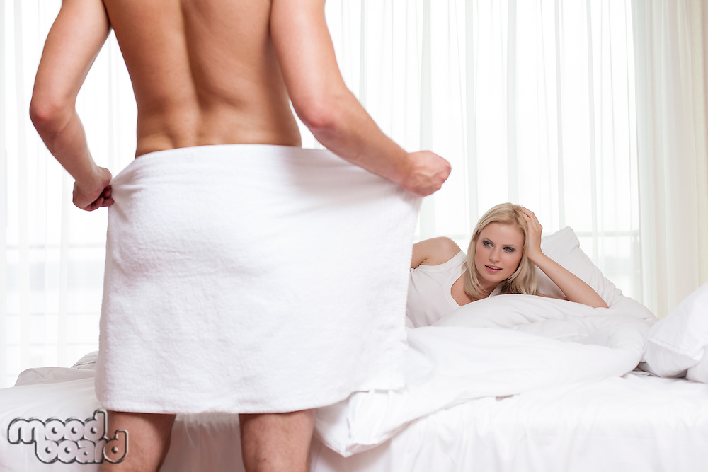 Young man looking at naked man holding towel in bedroom