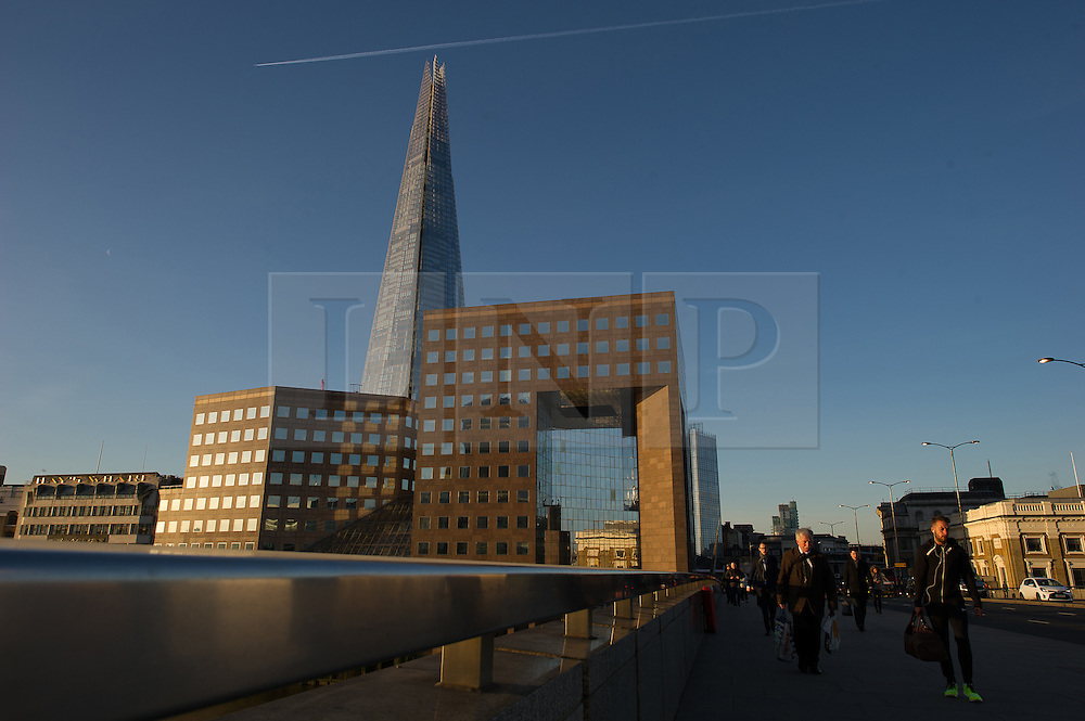 © London News Pictures. 03/04/15. London, UK. Commuters cross over London Bridge during sunrise, City of London. Photo credit: Laura Lean/LNP