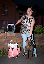 © Licensed to London News Pictures. 25/09/2014. Bristol, UK.  Heidi Beacham of Fisher Avenue waits with her Staffie cross dog Ruby, cat and 5 kittens, after leaving her home during flooding in Fisher Road and Fisher Avenue from a burst water main.  Many people were evacuated from their homes, some by boat, as water came up as high as their windows . Photo credit : Simon Chapman/LNP