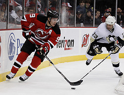 Dec 30, 2009; Newark, NJ, USA; New Jersey Devils left wing Zach Parise (9) skates with the puck away from Pittsburgh Penguins right wing Bill Guerin (13) during the first period at the Prudential Center.