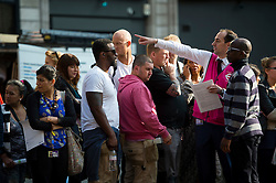 © Licensed to London News Pictures. 09/07/2015. London, UK. People queue for a bus as a TFL employee offers assistance to a traveller. Commuters stranded at Victoria Station in London on the day of a network wide tube strike which finishes at 9.30 this evening. Photo credit: Ben Cawthra/LNP