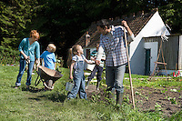 Parents with three children (5-9) gardening outside cottage