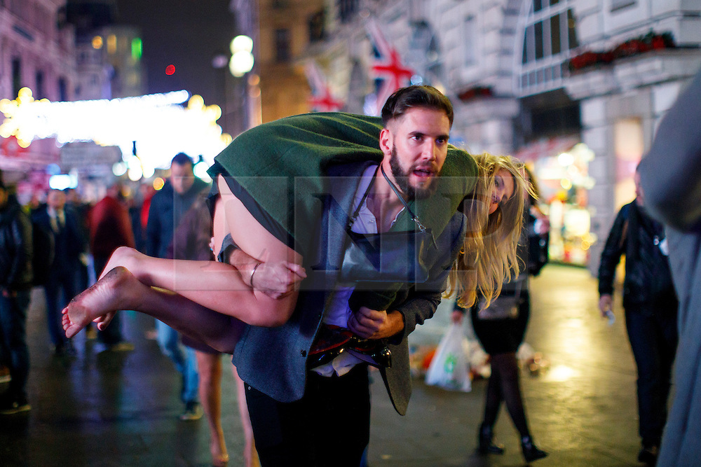 © Licensed to London News Pictures. 01/01/2017. London, UK. An intoxicated reveller is carried as people celebrate the New Year in central London during the first hours of 2017 on January 1. Photo credit: Tolga Akmen/LNP