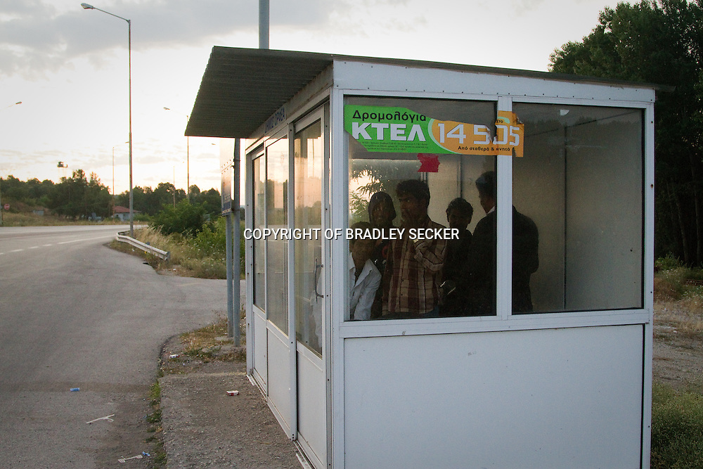 A group of 7 Bangladeshi men change out of their wet clothes in a bus shelter after swimming across the Evros river into Greece. Mandra, Evros, Greece. July 2011