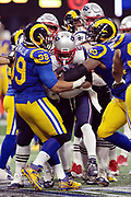 New England Patriots running back James White (28) gets gang tackled by Los Angeles Rams defensive end Aaron Donald (99) and Rams defensive end Michael Brockers (90) as he runs the ball during the NFL Super Bowl 53 football game on Sunday, Feb. 3, 2019, in Atlanta. The Patriots defeated the Rams 13-3. (©Paul Anthony Spinelli)