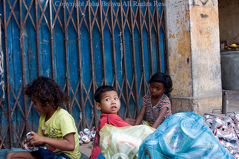 Young children who are scavengers are smashing aluminum cans on a city street in Kampong Cham, Cambodia.