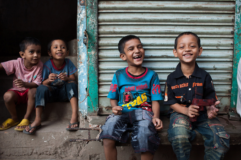 Young Bangladeshi friends laugh and joke late afternoon in the historic old city of Dhaka in Bangladesh