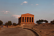 Low angle view of the Temple of Concord, 5th century BC, Agrigento, Sicily, Italy,  pictured on September 11, 2009, in the warm evening light. Well preserved owing to its 6th century AD conversion to a church, the Temple of Concord is a typical example of optical correction whose tapering columns create the illusion of a perfectly aligned building. Its frieze consists of alternating triglyphs and metopes, and the pediment is undecorated. The Valley of the Temples is a UNESCO World Heritage Site. Picture by Manuel Cohen.
