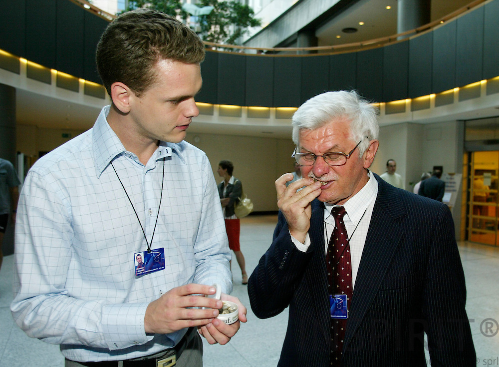 BRUSSELS - BELGIUM  -27 AUGUST 2004--Swedish MEP Christofer FJELLNERs(L) shows how mouth tobacco the Swedish Snus is used to his fellow MEP from Poland Zbigniew ZALESKI(R). Christofer FJELLNER was selling the Snus in the European Parliament as a protest against the EU-ban that it may not be sold in other EU countries than Sweden and Denmark.--PHOTO: ERIK LUNTANG