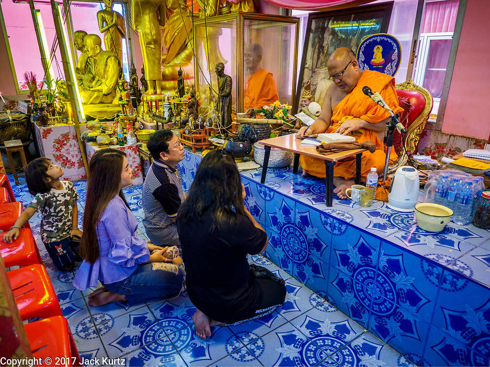 """24 JUNE 2017 - BANG KRUAI, NONTHABURI: A Buddhist monk talks to people after a rebirthing ceremony at Wat Ta Kien (also spelled Wat Tahkian), a Buddhist temple in the suburbs of Bangkok. People go to the temple to participate in a """"Resurrection Ceremony."""" Thai Buddhists believe that connecting people by strings around their heads, which are connected to a web of strings suspended from the ceiling, amplifies the power of the prayer. Groups of people meet and pray with the temple's Buddhist monks. Then they lie in coffins, the monks pull a pink sheet over them, symbolizing their ritualistic death. The sheet is then pulled back, and people sit up in the coffin, symbolizing their ritualist rebirth. The ceremony is supposed to expunge bad karma and bad luck from a person's life and also get people used to the idea of the inevitability of death. Most times, one person lays in one coffin, but there is family sized coffin that can accommodate up to six people. The temple has been doing the resurrection ceremonies for about nine years.     PHOTO BY JACK KURTZ"""
