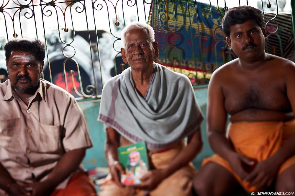 Three Hindu devotees sit in front of a Hindu temple in Thiruvannamalai, Tamil Nadu, India. December 27, 2007